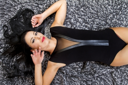 View of a beautiful young woman posing on top of a cool carpet. photo