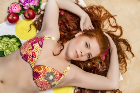 Portrait of a beautiful natural redhead woman with a bikini.  photo