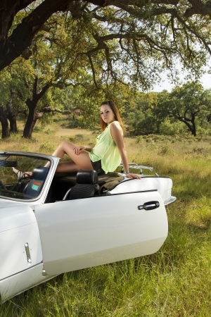 View of a beautiful woman posing on a white convertible car. photo