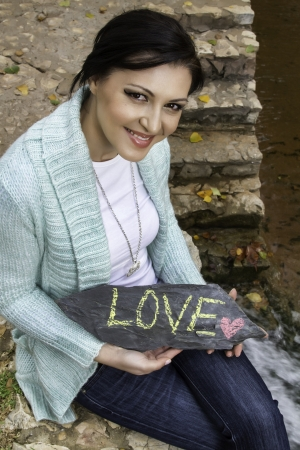 average woman: Happy young woman showing the words, Love, on a stone. Stock Photo