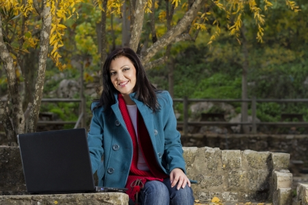 average woman: View of a beautiful young woman working on a laptop on a urban park.