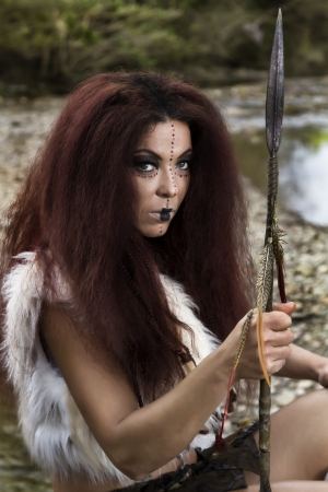 View of a beautiful young strong hunter warrior woman next to a river.