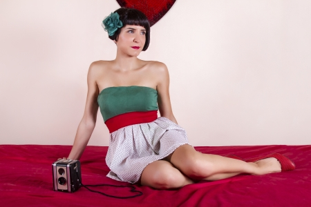 View of a pin-up girl in bed with small retro camera. photo