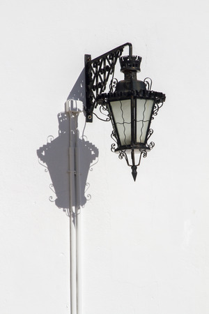 Close up view of a vintage streetlight over a white wall. Stock Photo