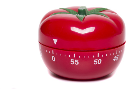 Close up view of a tomato kitchen clock timer isolated on a white background.