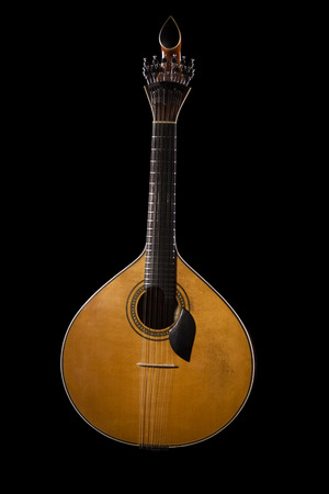 Close view of a traditional Portuguese guitar on a dark .