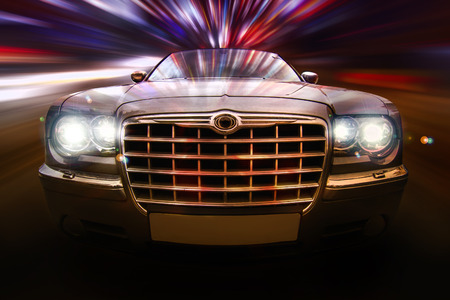 car grill: Close up frontal view of a speeding car on the night.