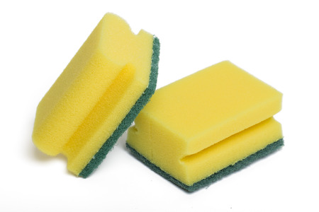 Close up view of a yellow cleaning sponge isolated on a white . photo