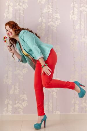 View of a beautiful redhead girl with a lollipop candy wearing colorful clothing. photo