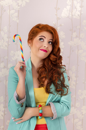candy stick: View of a beautiful redhead girl with a candy stick wearing colorful clothing.