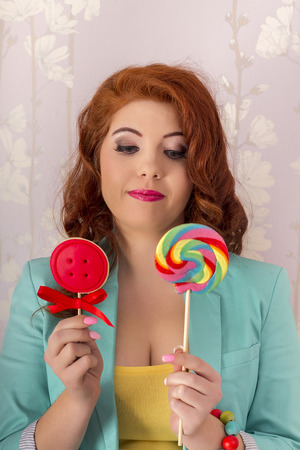 View of a beautiful redhead girl with two lollipop candies wearing colorful clothing. photo
