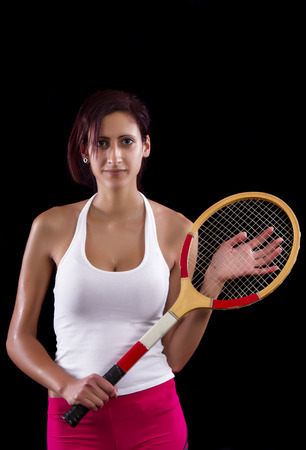 Beautiful young girl with a tennis racquet on a black background. photo