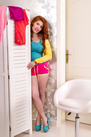View of a beautiful redhead girl in her colorful bedroom.