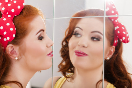 View of a beautiful redhead girl with colorful pinup clothes next to a mirror wall. photo
