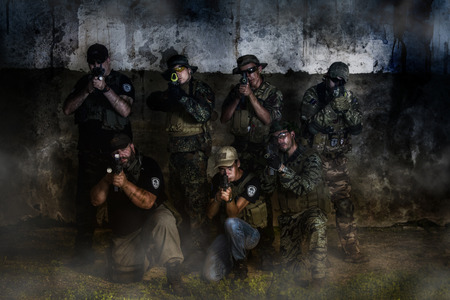 gritty: Large Airsoft group team posing to the camera with a gritty and grunge effect.