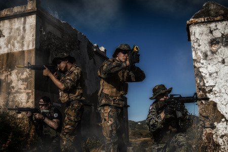 gritty: Airsoft group team in daytime action walking in terrain recognition  with a gritty and grunge effect.