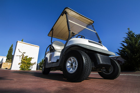 Close up view of a white golf cart parked on the road. photo