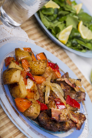 Close up view of oven baked meat with potatoes, and watercress salad. photo