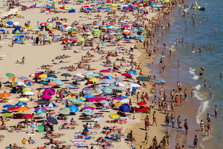 Broad view of a crowded beach on Portimao, Portugal.