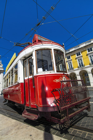trams: View of the vintage famous red electrical trams circulating still today in Lisbon, Portugal.