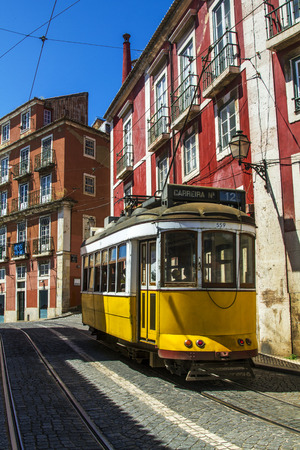 trams: View of the vintage famous yellow electrical trams circulating still today in Lisbon, Portugal.