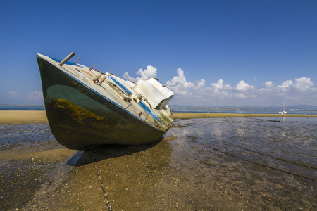 View of an old abandoned boat stranded on dry sand at the beach.