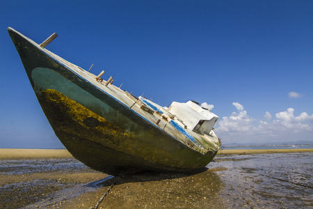 ria: View of an old abandoned boat stranded on dry sand at the beach.