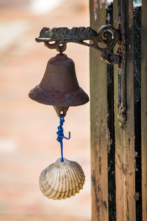 door bell: Close up view of a small rusty bell with a shell serving as a door bell. Stock Photo