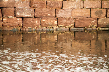 submerge: View of red stone brick wall from a building creating a reflection on the water.