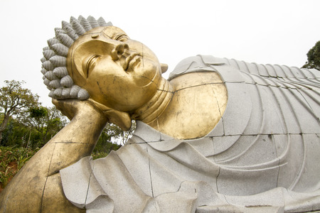Close up view of a beautiful reclining  Buddha statue on a park.