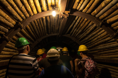 tunneling: View of a dark eerie mining tunnel with tourists.
