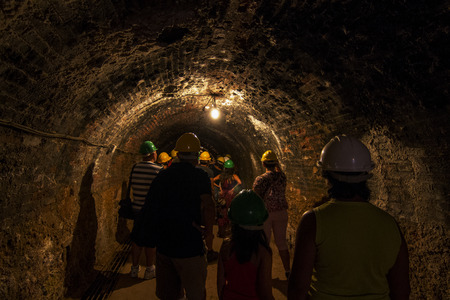 View of a dark eerie mining tunnel with tourists. photo