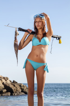 Beautiful view of a young girl in a bikini holding a freshly caught octopus.