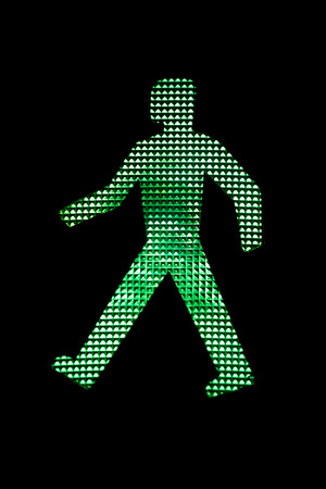 rules: Close view of a pedestrian traffic light green man.