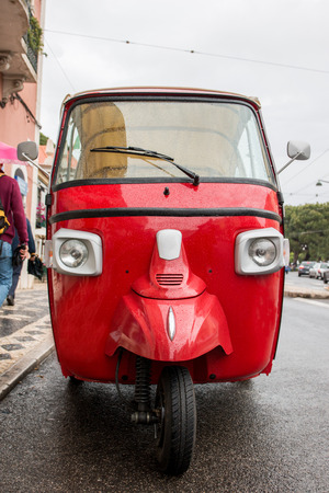 three wheeler: Close up front view of a red vintage auto rickshaw motorcycle on Lisbon.