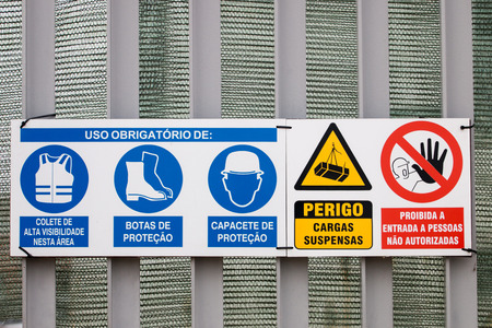 overload: Several safety and warning signs on a construction site on Portuguese language.