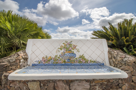 azulejo: Beautiful view of a portuguese azulejo bench on a white cloudy landscape with palm tree bushes. Stock Photo
