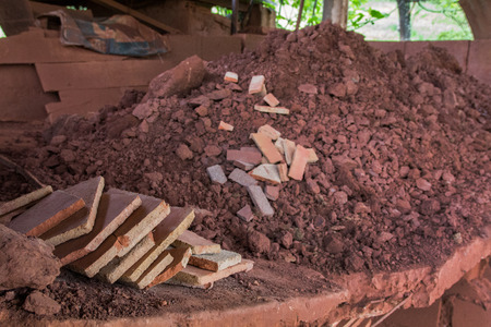 dirt pile: Red dirt pile and mud bricks in a table ready for transformation.
