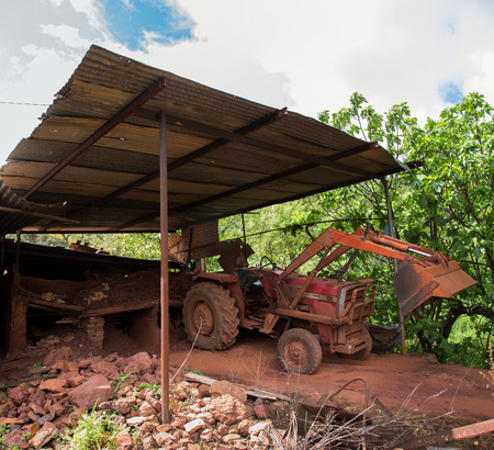 dirt pile: Red dirt pile in a table ready for transformation and tractor. Stock Photo