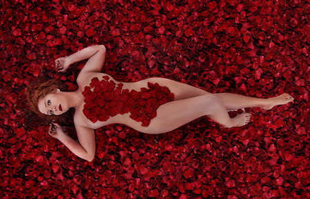 nude young woman: Close up view of a sensual nude young woman covered in rose petals.