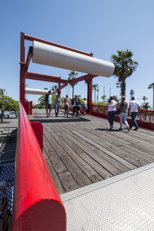colom: View of a red bridge for pedestrians on Passeig de Colom, located in Barcelona, Spain.