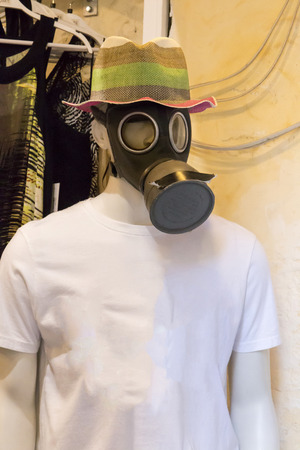 male mannequin: Close view of a crazy male mannequin with a colorful hat and a gas mask.