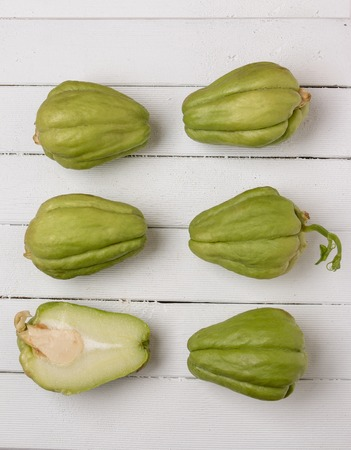 chayote: Close view of a chayote fruit on white wooden background.