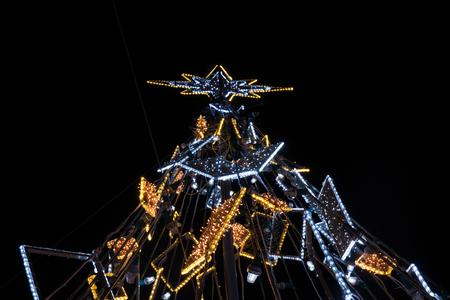 fake christmas tree: Upward view of a illuminated fake Christmas tree at night.