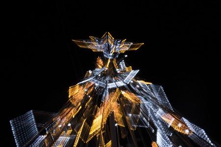 fake christmas tree: Upward view of a illuminated fake Christmas tree at night with zoom effect. Stock Photo