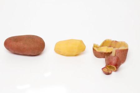pealing: Close up view of the potato pealing process on a white background.