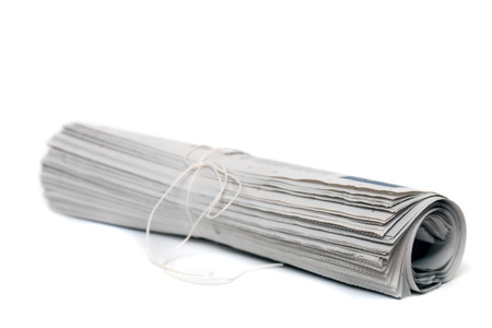 newspaper: Close view of a rolled up newspaper with string isolated on a white background.