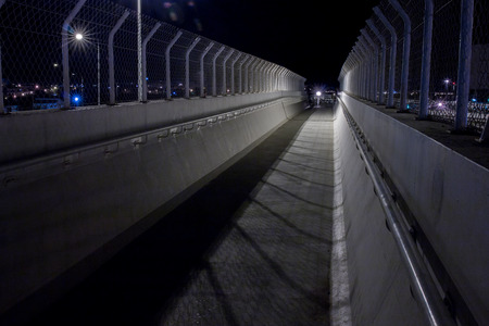 pedestrian bridges: View of the corridor of a bridge with fence protection in the evening.