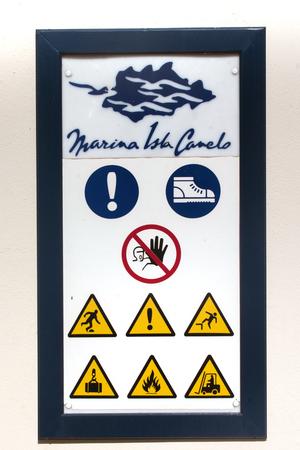 peril: Close up view of a warning sign near a marina, depicting several warnings.
