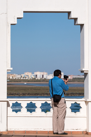 moral: Man taking a photograph to the village in Isla del Moral, Spain.